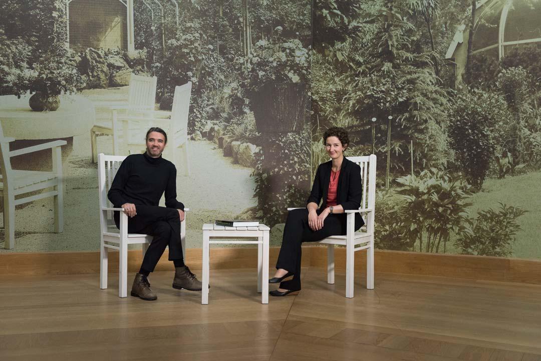 Die Kuratoren der Ausstellung Dr. Roman Zieglgänsberger und Dr. Sibylle Discher vor einer Ansicht des Gartens Heinrich Kirchhoffs (auf Fototapete). Foto: Bernd Fickert/Museum Wiesbaden