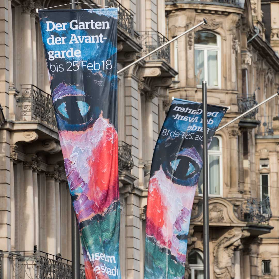 Das bereitet Freude: die Fahnen, die auf der Wiesbadener Wilhelmstraße für die Kirchhoff-Ausstellung werben (Foto: Museum/Bernd Fickert)
