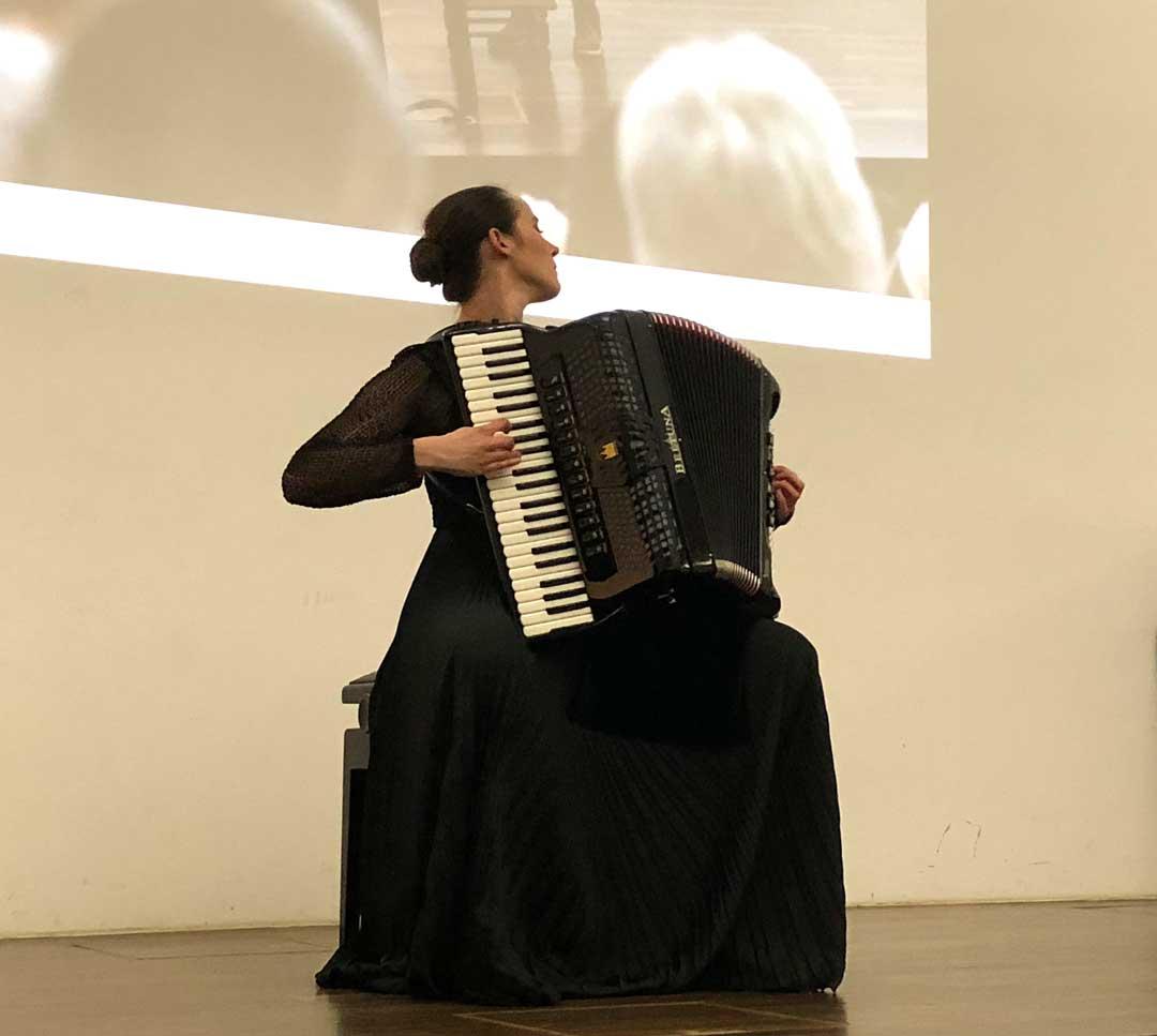 Stefanie Hazenbiller mit beeindruckendem Akkordeonspiel vor großer Wandprojektion