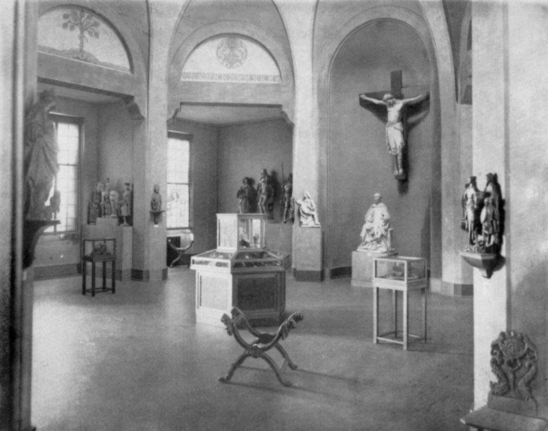 Der Kirchensaal im Jahr 1921: in der Nische im Hintergrund Kruzifix aus Walsdorf, um 1200, darunter Steinfigur eines Klerikers (Hl. Bernhard?) aus Eberbach, im Vordergrund gotischer Faltstuhl aus Limburg