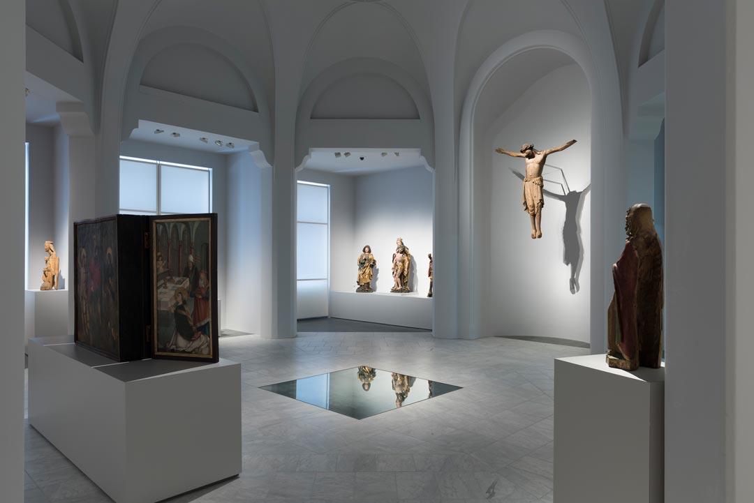 Der Kirchensaal heute: im Hintergrund das Walsdorfer Kruzifix sowie eine Gruppe aus Gnadenstuhl, Heiligem Johannes und Heiligem Viktor, um 1500 (Foto: Bernd Fickert/ Museum Wiesbaden)